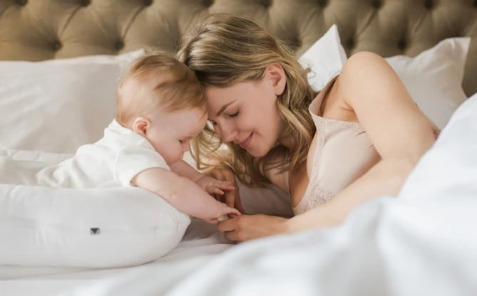 A woman cuddles with her baby on a bed.