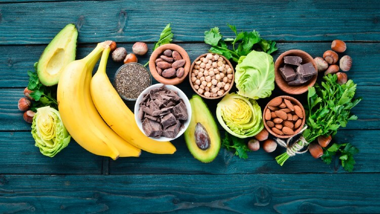 Foods containing natural magnesium. Mg: Chocolate, banana, cocoa, nuts, avocados, broccoli, almonds. Top view. On a blue wooden background. Y