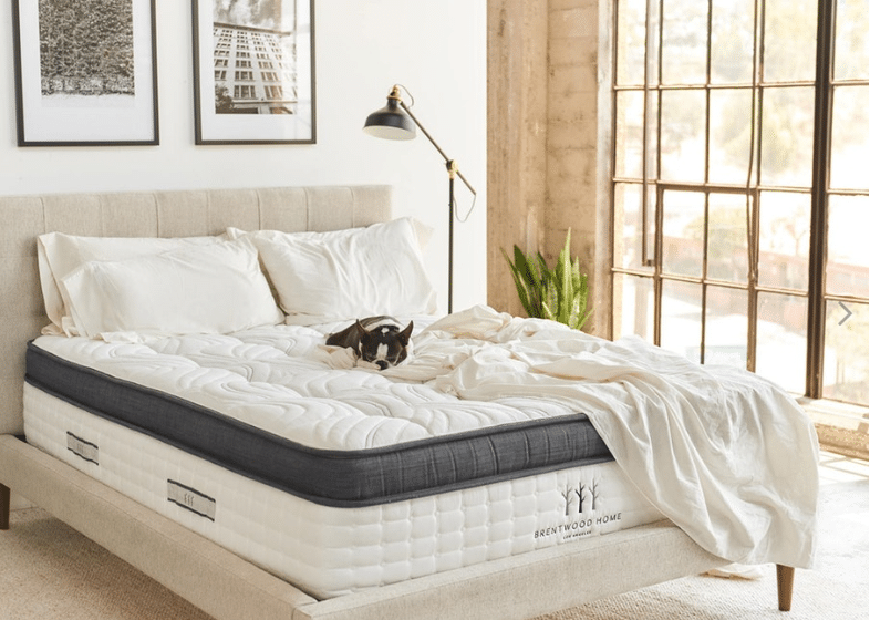 A white hybrid mattress in a bedroom.