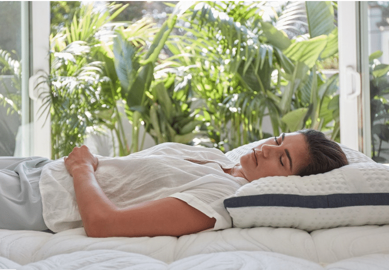 A woman sleeping on a white hybrid mattress in front of green plants.