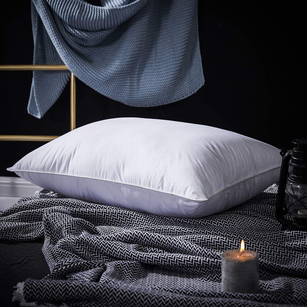 PALAWRAN down cushion with Egyptian cotton shell resting on dark bedsheets next to a lit candle.