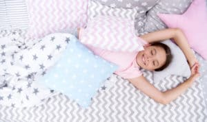 A girl sleeping on flannel sheets with throw pillows and a blanket.