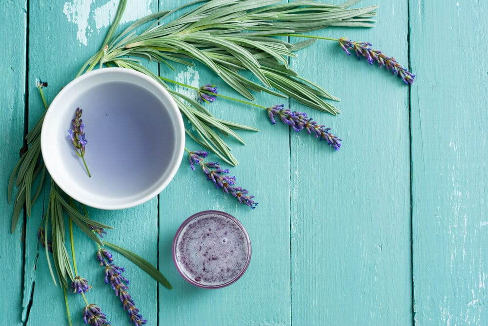 cup of lavender tea, flowers and syrup on blue wooden table background