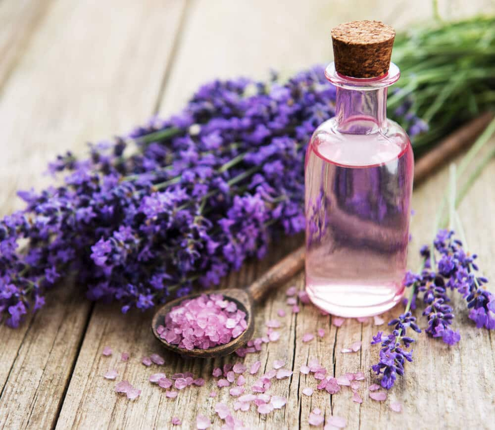 sea salt, essential oils and fresh lavender flowers on a old wooden background