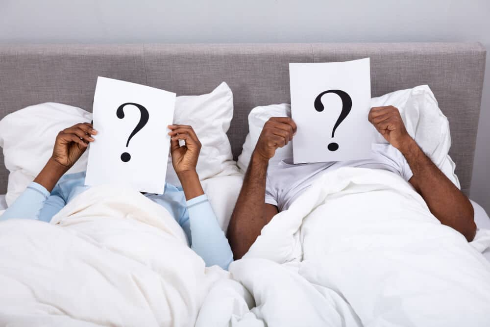 Couple Lying On Bed Holding Question Mark Sign In Front Of Their Face