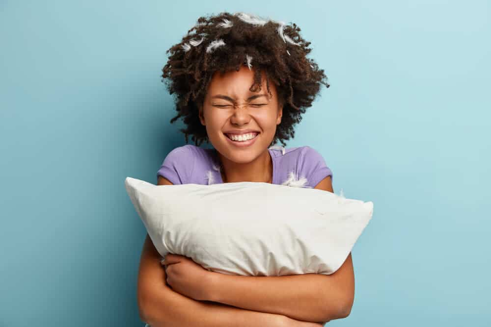 Photo of joyful impressed cheerful woman smiles broadly, has pillow fight, feathers stuck in curly hair, dressed casually, isolated over blue background. Happiness, sleeping and rest concept