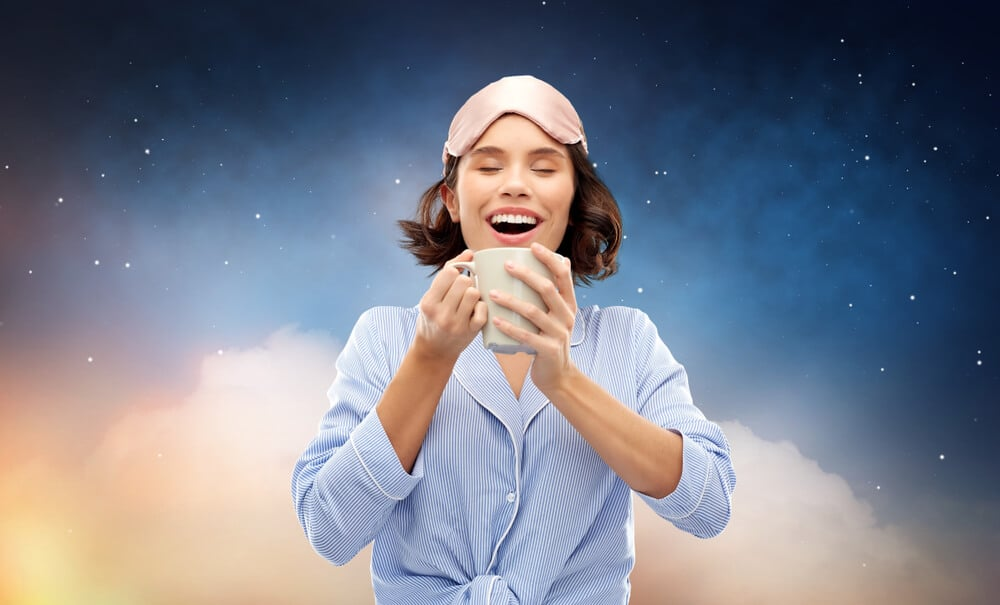 people and bedtime concept - happy young woman in pajama and eye sleeping mask drinking coffee from mug over starry night sky and cloud background; tea for sleep concept.