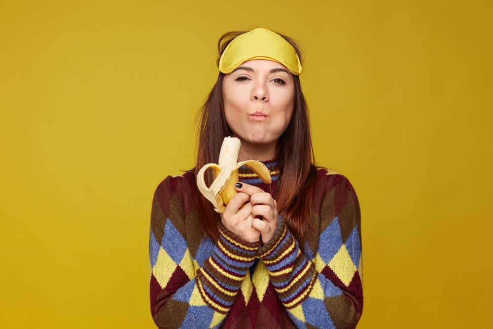 Lovely mixed race young woman holds delicious banana, tastes with pleasure, enjoying likes eating sweets, has good appetite, wears colorful sweater and sleeping mask on head. Healthy eating concept.