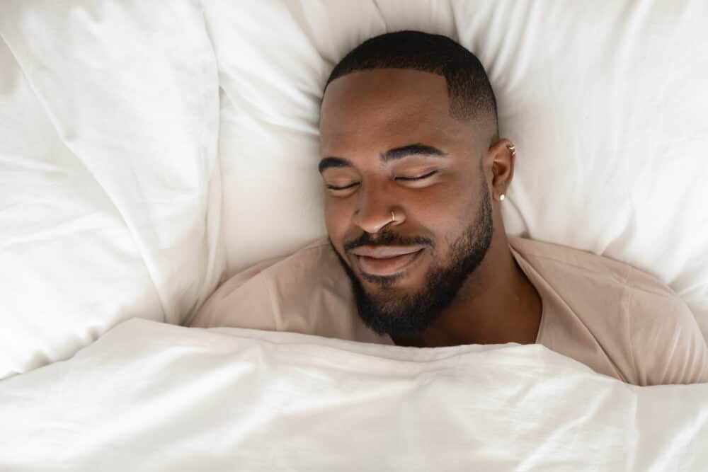 Top view of happy african American man sleeping in comfortable white bed seeing good pleasant dreams, calm biracial male feel fatigue resting napping in cozy bedroom under linen bedding sheets; getting better sleep after CBT I.