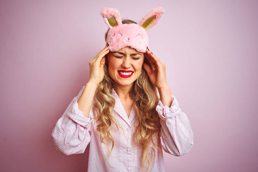 A woman in pajamas holds her hands to her head with a pained expression against a pink background; excessive sleep increases stroke risk concept.