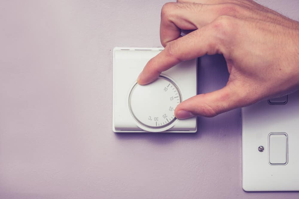 Hand turning dial on thermostat, best temperature for sleep concept.