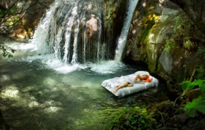Sleeping woman in deep forest with waterfall on back; nature sounds for sleep concept.