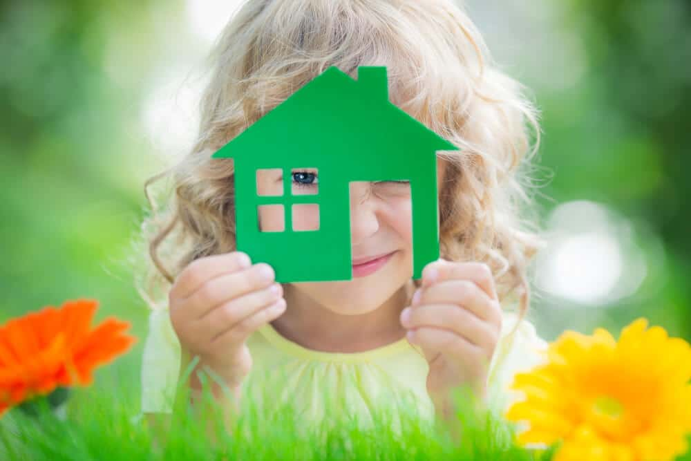 Happy child holding house in hands against spring green background. Eco friendly bedroom upgrades concept.