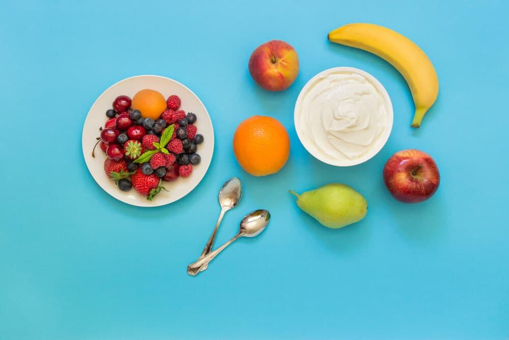 Greek yogurt around orange, banana, pear, peach, apple, plate of strawberries, raspberries, blueberries and 2 spoons on light blue background. Yogurt and fruits, berries as an ingredients. Top view.