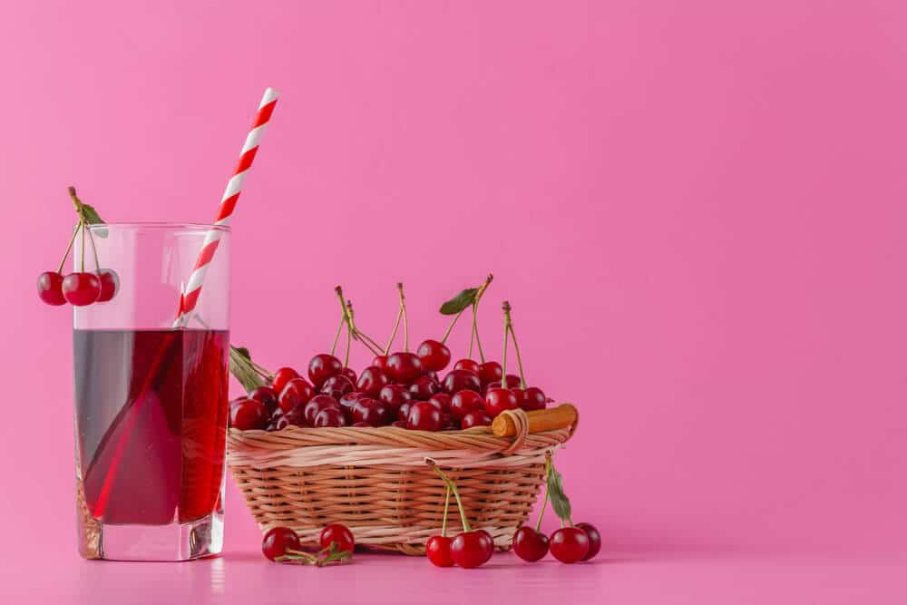Tart cherry juice in a glass and pitcher on pink with ripe berries in wicker basket