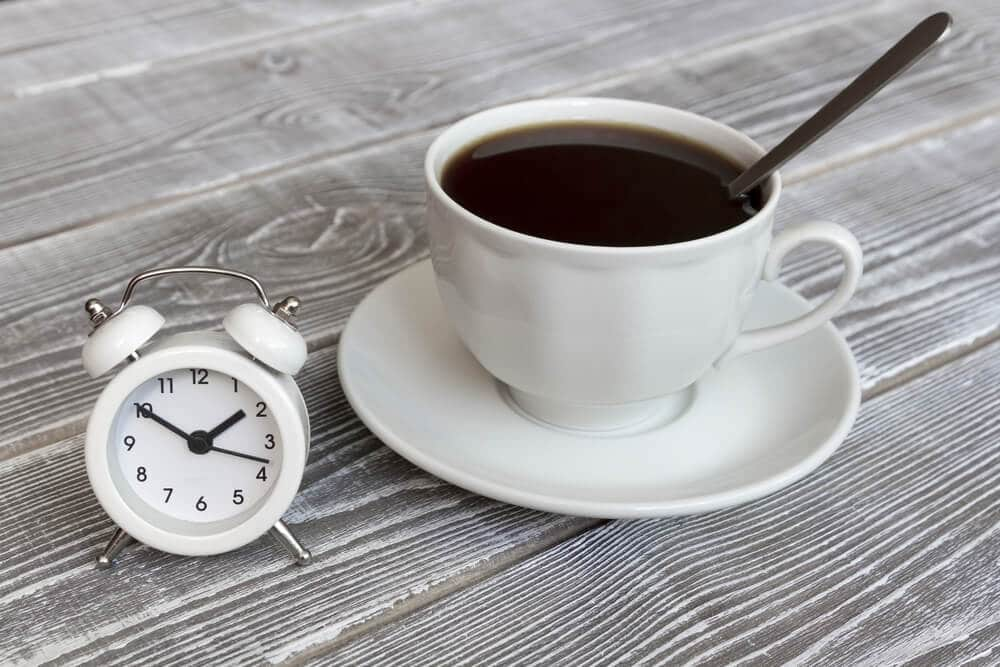 A cup of coffee with an alarm clock on the background of a wooden table.