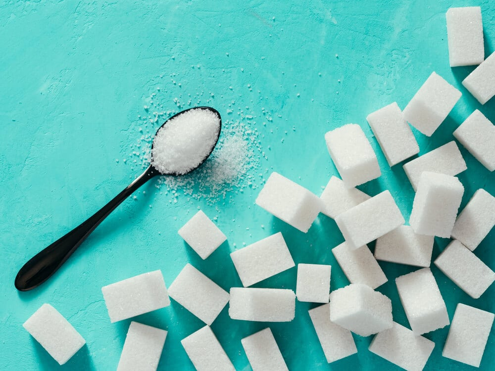 background of sugar cubes and sugar in spoon. White sugar on turquoise background. Sugar with copy space. Top view or flat lay