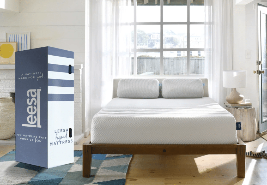 A white Leesa Legend hybrid mattress on a wooden bed frame with a blue and white box.