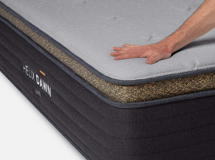 A hand presses on a firm Helix Luxe mattress for stomach sleepers.