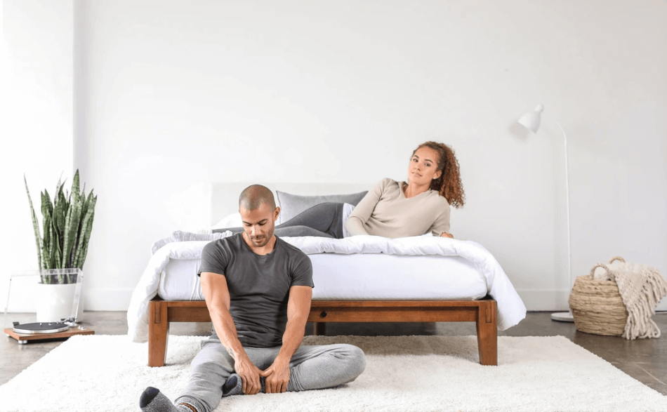 Two people relax with their Thuma bed frame.
