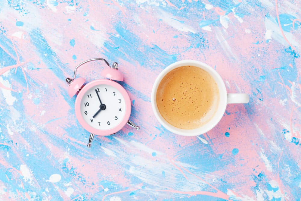 Morning cup of coffee and alarm clock on colorful working desk top view in flat lay style. Punchy pastel background.