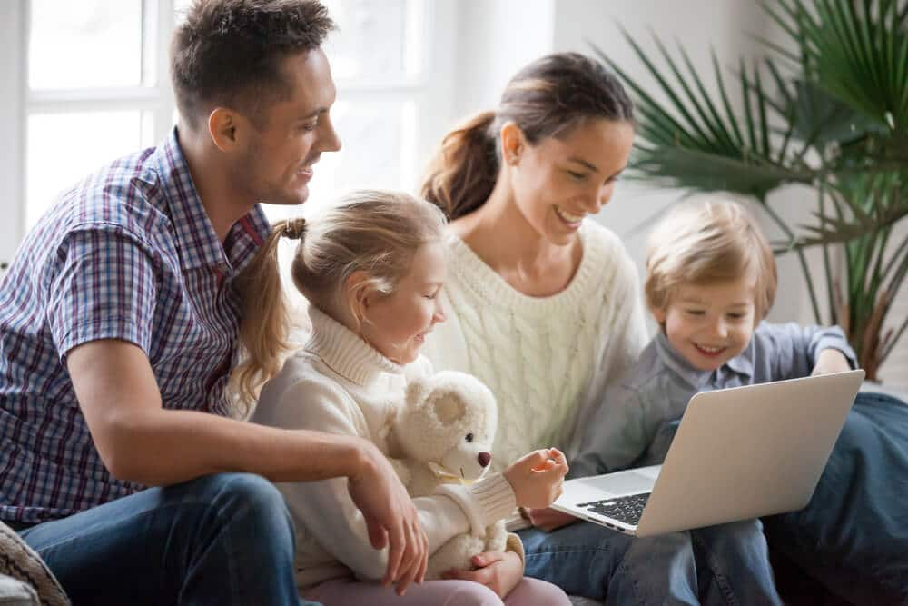 Two parents with two kids looking at a laptop and smiling.