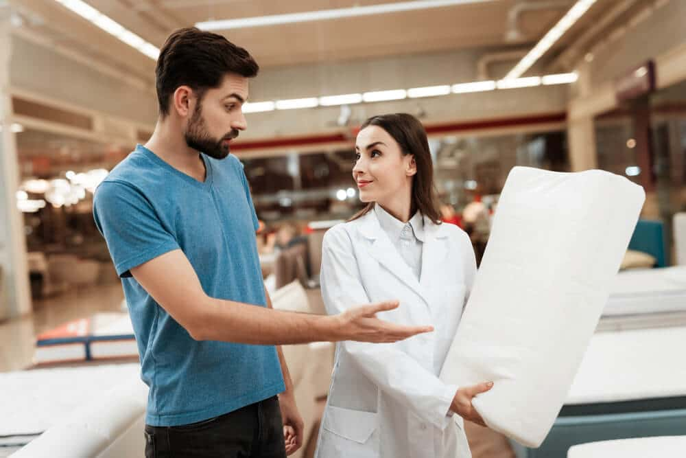 Lovely girl consultant demonstrates orthopedic pillow to confident man in furniture store. Purchase of orthopedic pillow . Choosing pillow in store.
