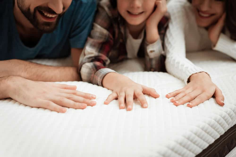 A couple with their daughter looking at a white mattress.