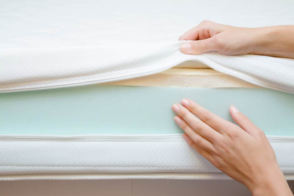 Woman's hands touching different layers of new foam mattress. Checking hardness and softness. Choice of the best type and quality. Front view. Close up.