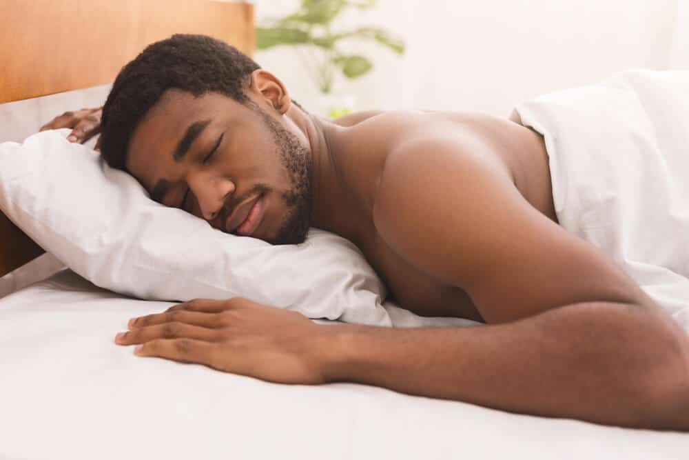 Portrait of african-american man sleeping shirtless on stomach in bed at home, closeup