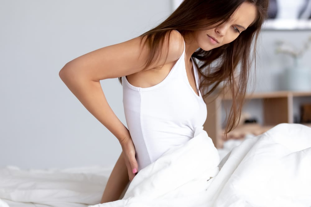 A woman wearing a white tank top and rubbing her back while sitting up on a white mattress with a white cover.
