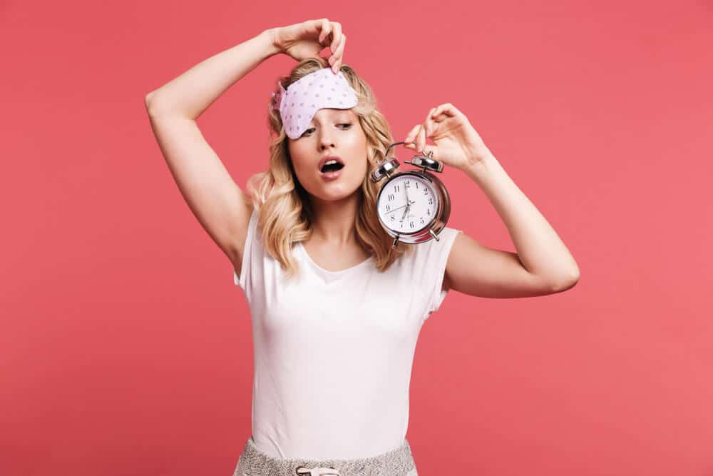 Portrait of blond young woman 20s wearing sleeping mask holding alarm clock after awakening isolated over red background