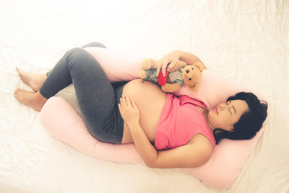 Happy pregnant woman sleeping on bed in bedroom at home for resting and stress relief. The young expecting mother holding baby in pregnant belly. Maternity prenatal care and woman pregnancy concept. B