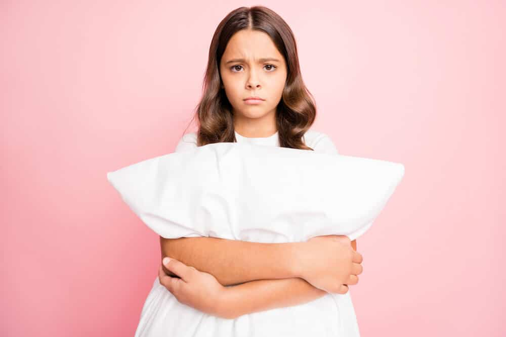 A young girl holding a white pillow and frowning in front of a pink background.