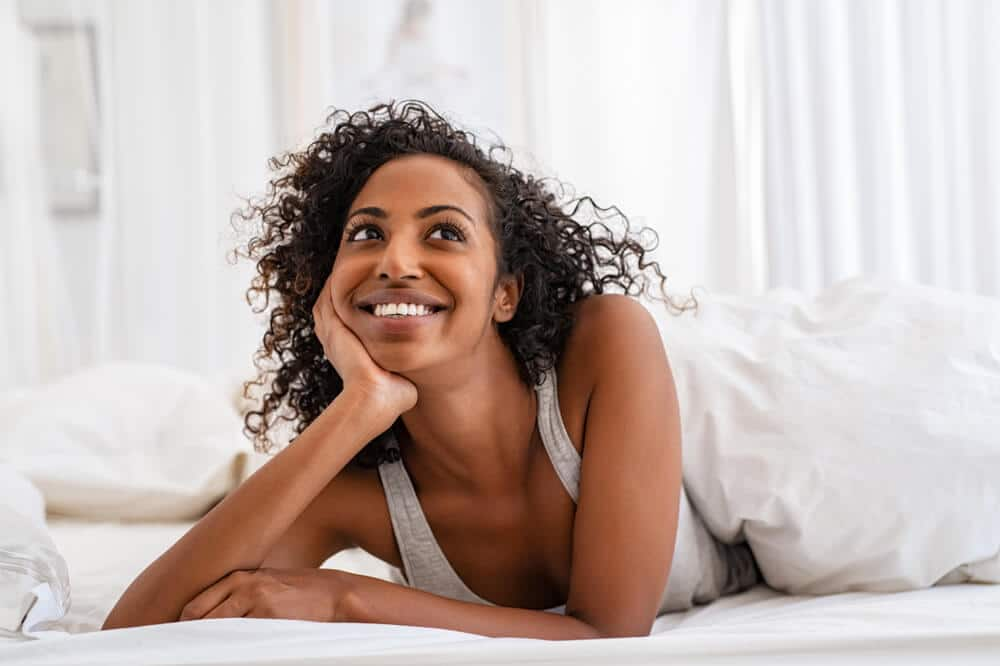 A smiling Black woman resting on her mattress.