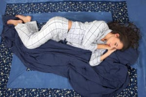 Woman sleeping in side position, in comfort on bed