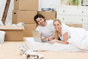 A couple sitting on a mattress with boxes surrounding them.