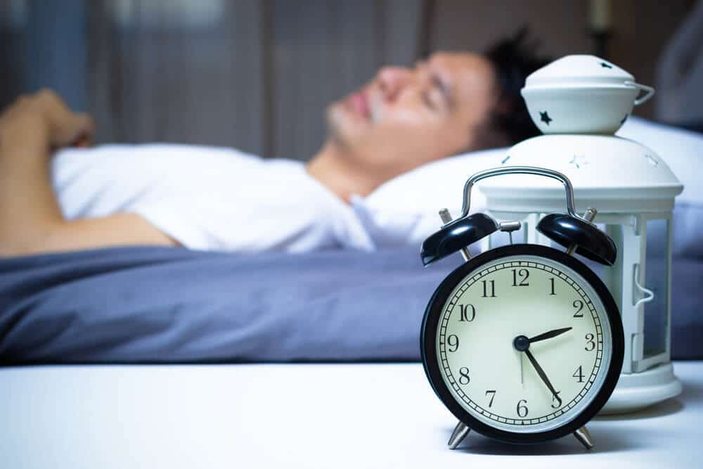 sleeping asian man in bed at night