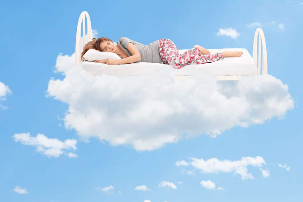 Relaxed young woman sleeping on a comfortable best foam mattress in the clouds