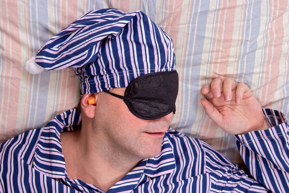 Man sleeping with a mask on eyes. Man in striped pajamas sleeping in bed with a night cap and eye protection blindfold. Above portrait dreaming happy man with eye patch.
