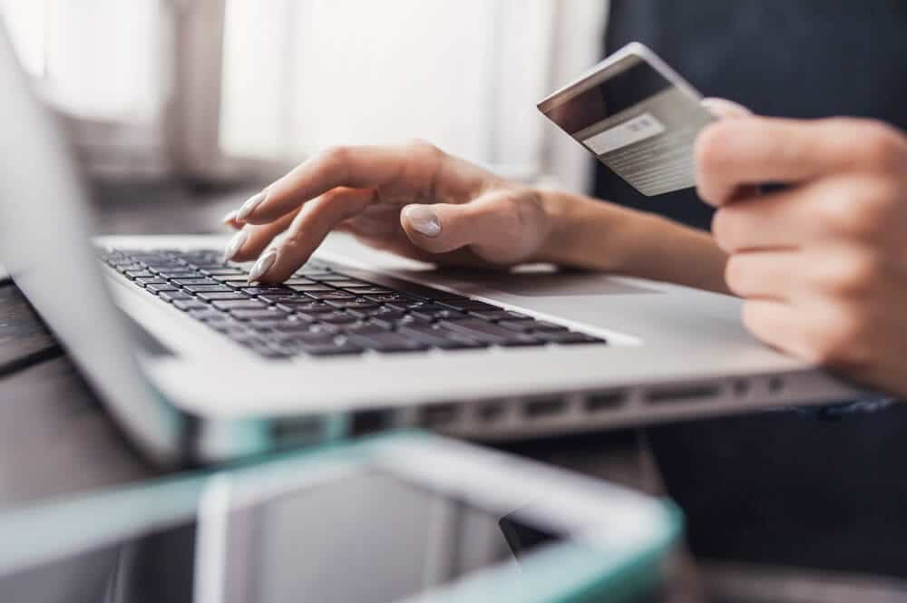A person typing on a laptop and holding a silver credit card to buy something online.