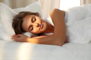 A woman sleeping on a mattress with a white comforter.