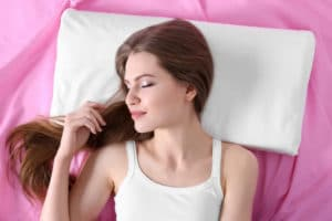 Young woman sleeping on orthopedic pillow. Healthy posture concept