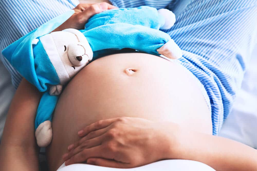Close-up pregnant woman's belly with teddy toy bear. Beautiful pregnant woman sitting at bed and holds hands on belly in bedroom at home. Pregnancy, parenthood, preparation and expectation concept. N