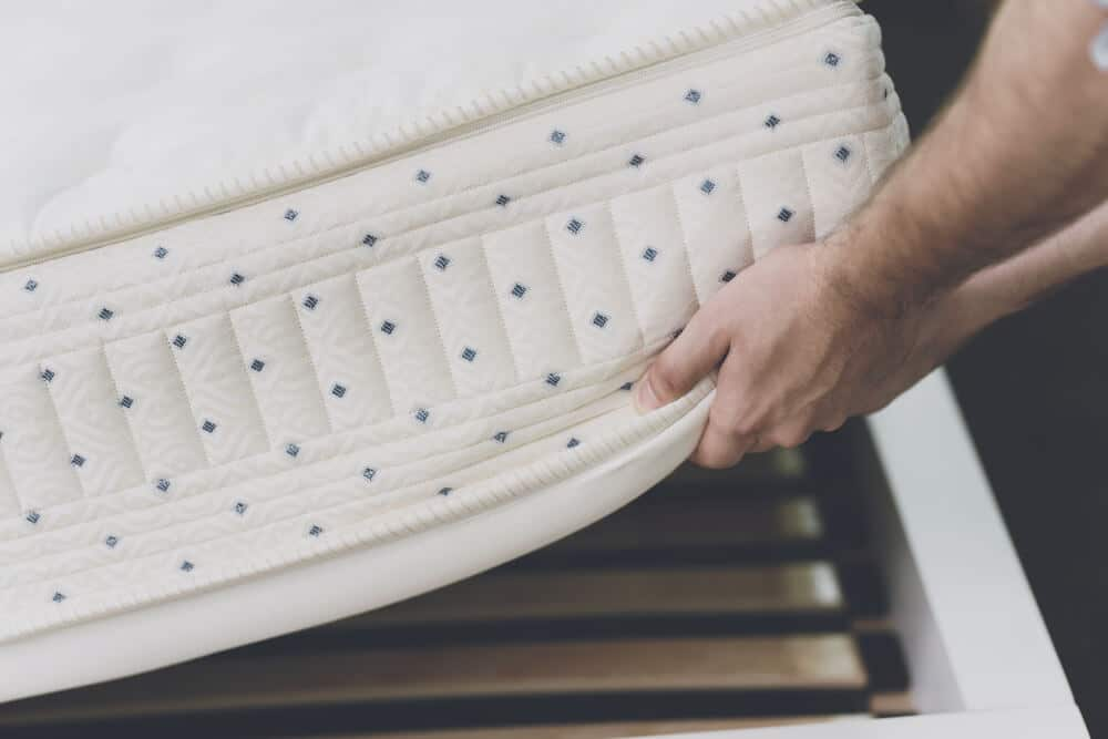 A person setting a white mattress with blue dots on top of a slatted bed frame.