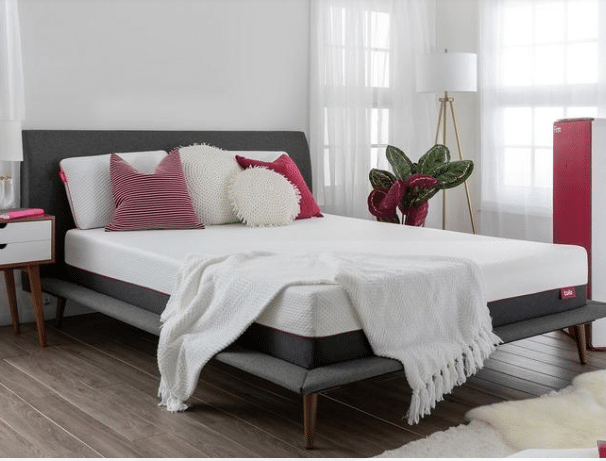 A white Tulo Firm mattress with pink and white pillows, a white throw and a gray mattress frame.