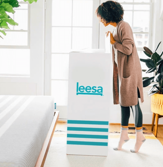 A woman opening a white and turquoise Leesa Mattress box.