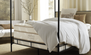 A white Saatva mattress on a black four-post bed frame.