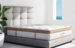 A brown and white Saatva HD mattress on a fabric bed frame.