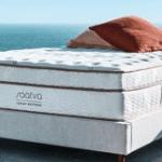 A white Saatva original mattress with red pillows.